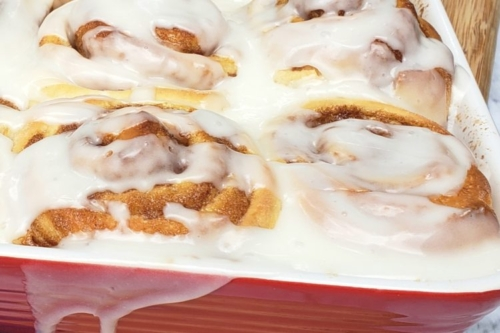 Cinnamon Rolls slathered with icing in a baking dish