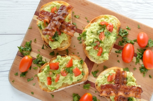 Bacon Avocado Toasts on a wooden cutting board