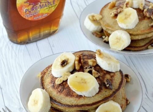 Pancakes on a plate with sliced bananas on top