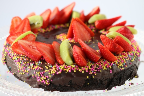 Birthday Chocolate Cake topped with sliced strawberries and kiwi