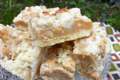 stacked Salted Peanut Caramel Shortbread Crumb Bars on a plate