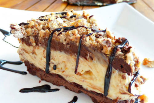 a slice of Snickers and Peanut Butter Cheesecake on a plate