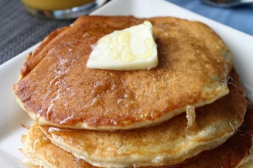 A stack of Buttermilk Pancakes on a plate with a pat of butter