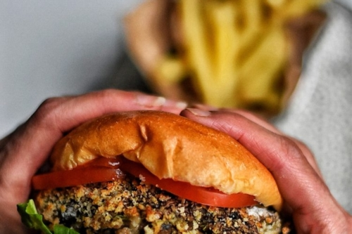 two hands holding a Portobello Mushroom Burger