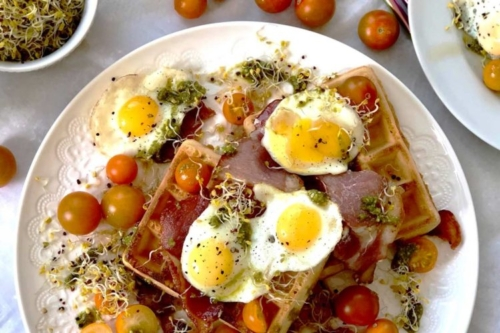 Waffle, Quail Eggs, Bacon and Maple Syrup on a plate