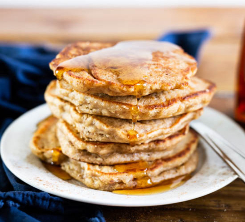 stacked Apple Cider Pancakes on a plate with syrup