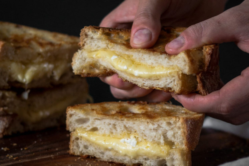hands holding a Gooey Grilled Cheese Sandwich