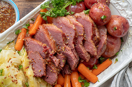 a platter of corned beef, cabbage, potatoes and carrots