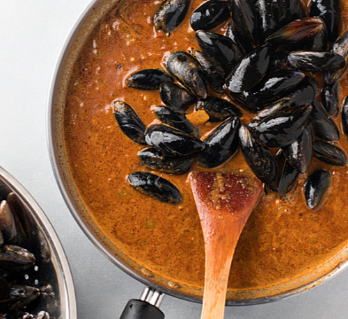 Thai Curry in a pan topped with mussels