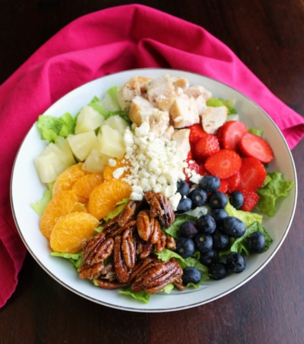 a bowl of fruit, berries, chicken and pecans