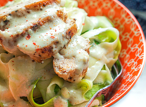 a bowl of zucchini noodles topped with chicken and alfredo sauce