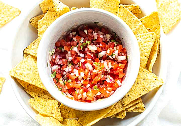 pico de gallo in a bowl surrounded by tortilla chips