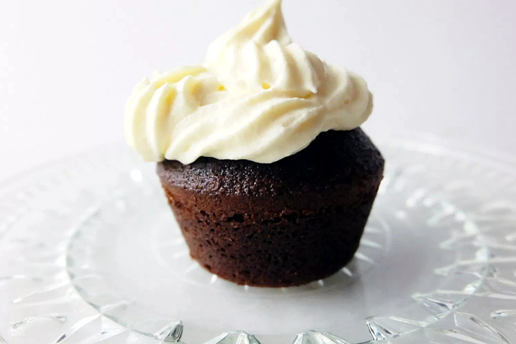 one chocolate cupcake on a plate with vanilla frosting