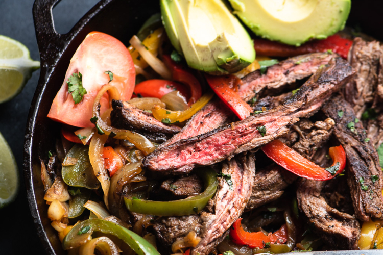 steak, peppers and onions in a skillet