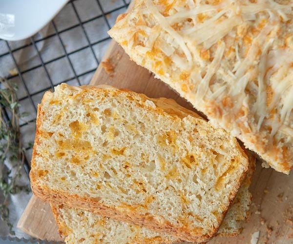 sliced cheddar cheese bread on a wooden cutting board