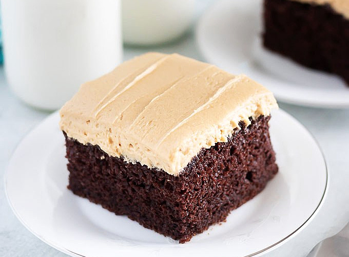 a slice of chocolate cake with peanut butter frosting on a plate
