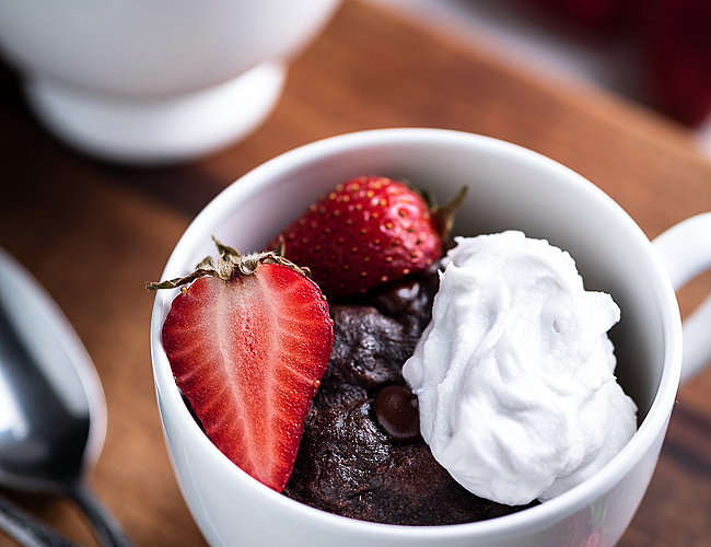 chocolate cake in a mug with whipped cream