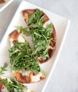 Prosciutto Pizza with Arugula on a platter
