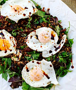 3 over-easy eggs over lentils, mushrooms and wasabirocket