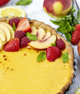 peach tart topped with fruit and berries