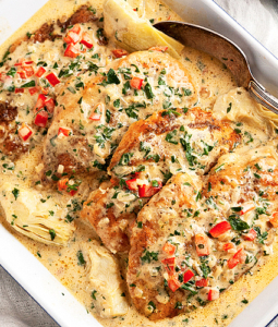 chicken breasts in a lemony, garlicky parmesan cream sauce with artichokes, red peppers, and parsley