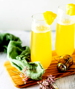 2 pineapple mimosas in tall glasses